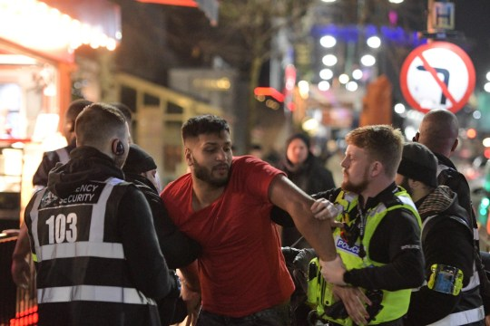 Pic by Michael Scott/Caters News - (PICTURED: Two men were ejected from Rosies Nightclub on Birminghams Broad Street during a Valentines Day event. The men were wrestled to the ground and one doorman punched a reveller in the face as he was restrained on the floor. Pic taken: 15/02/2019) - As thousands of revellers took to Broad Street in Birmingham on Valentines Day, a few partygoers took it too far, with two men being wrestled to the ground after being ejected from Rosies nightclub Footage shows the men being piled on by the bouncers in an attempt to stop them lashing out. At one point footage shows a bouncer, identified under the number 111, punching the reveller in the face as he is restrained on the floor. The revellers are later arrested and taken away, no action was taken against the bouncer at that time. Pictures also show Birmingham police officers ordering two men to pick up empty happy crack canisters that they disposed of out of their car whilst parked up on the nightclub strip. The car cruisers reluctantly swept up the capsules with their shoes and put them in their car before being ordered out of the area. ENDS