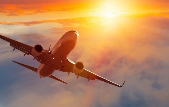 Airplane in the sky at sunset; Shutterstock ID 1005981310