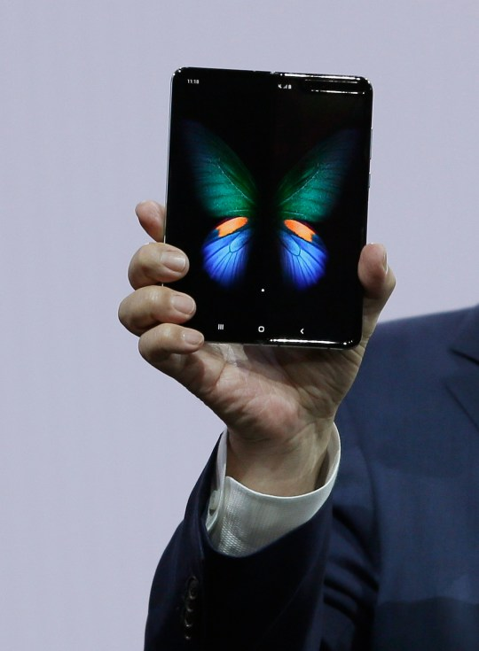 DJ Koh, Samsung President and CEO of IT and Mobile Communications, holds up the new Galaxy Fold smartphone during an event Wednesday, Feb. 20, 2019, in San Francisco. Samsung is hailing the 10th anniversary of its first smartphone with three new models that seem unlikely to reverse a sales slump in an industry recycling the same ideas. (AP Photo/Eric Risberg)