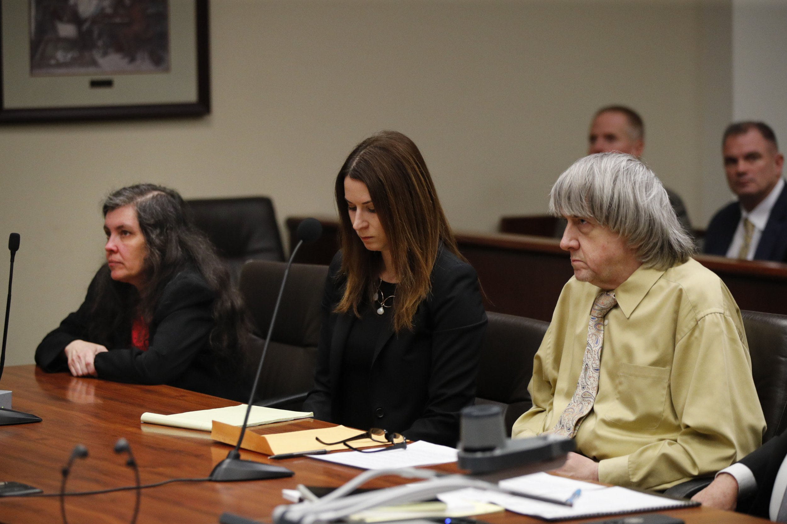 """David Turpin, right, and wife, Louise, left, listen to the judge, along with attorney Allison Lowe, during a courtroom hearing, Friday, Feb. 22, 2019, in Riverside, Calif. The California couple who shackled some of their 13 children to beds and starved them pleaded guilty Friday to torture and other abuse in a case dubbed a """"house of horrors."""" (AP Photo/Jae C. Hong, Pool)"""