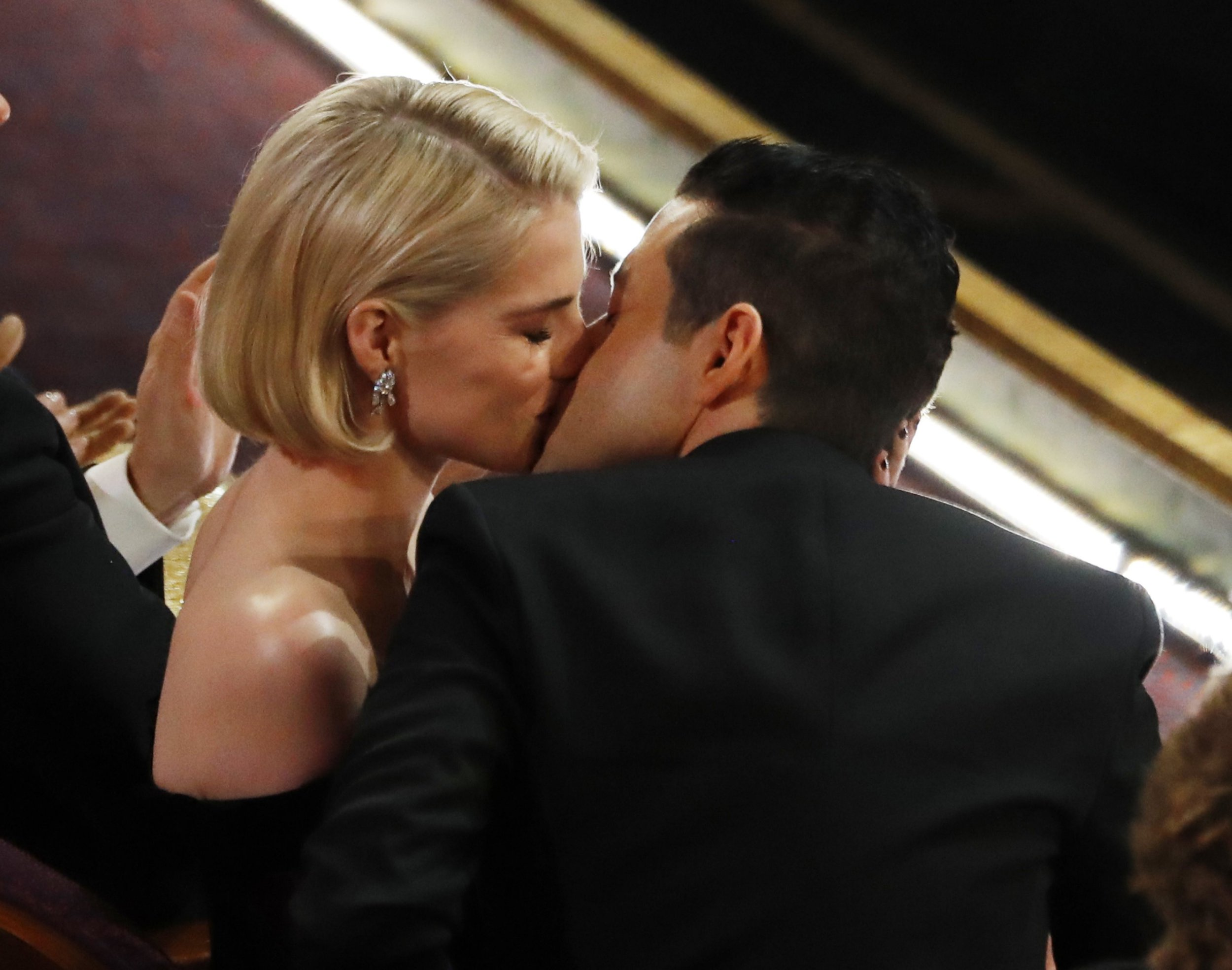 Rami Malek and Lucy Boynton treat Oscars like a school disco as they pack on the PDA