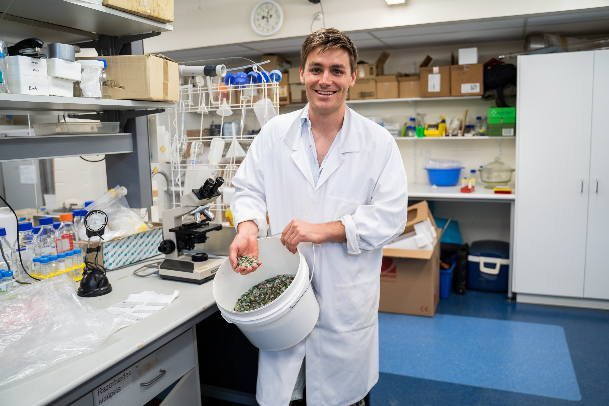 """PhD candidate Rhys Pirie. See National story NNglass; Scientists have invented a process that can turn waste glass into everything from toothpaste to car tyres. Glass is not always recyclable, leaving massive stockpiles with no use - but Australian researchers have now found a solution. PhD candidate Rhys Pirie said that a chemical found in 'drain cleaner' can break glass down and separate an amount of silica. This is then extracted for use in a commercial setting, meaning the liquid can be used for detergent, or even in crop fertilizer. Because of the effort required to sort out smaller fragments of glass, they tend to be discarded, stored, or sent to the landfill. Mr Pirie and Professor Damien Batstone from the University of Queensland were able to dissolve fragments into liquid silicate. Silicates are used in industry as adhesives, detergents, ingredients in cleaning compounds, cements, binders, and coatings. Mr Pirie said: """"We are taking waste glass that is currently going to the landfill because it is too small to be sorted into the right colour. """"We are dissolving it in a chemical most people know as drain cleaner - and once it's in that form it can be used to make things like tyres, detergent or silica gel. """"We can get all that silicate out of the glass. Glass is about 70 to 75 per cent silica. You need about 1.3kg of glass to make 1k of silica."""