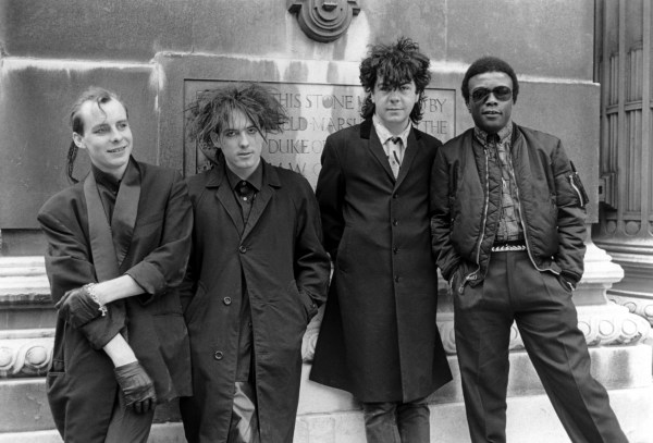 """The Cure - Paul """"Porl"""" Thompson, Robert Smith, Lol Tolhurst And Clifford Leon Anderson, Covent Garden - 1984, The Cure - Paul """"Porl"""" Thompson, Robert Smith, Lol Tolhurst And Clifford Leon Anderson, Covent Garden - 1984 (Photo by Brian Rasic/Getty Images)"""