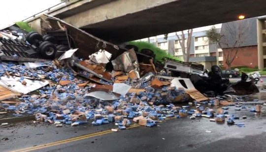 Huge truck full of beer overturns and spills booze all over busy