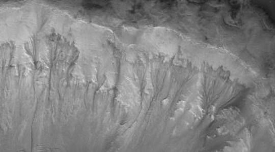 Uma visão dos vestígios de água manchados nas paredes da cratera em Marte (Imagem: Nasa)