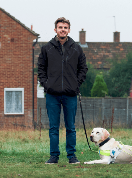Alex Pepper stands with his guide dog, River