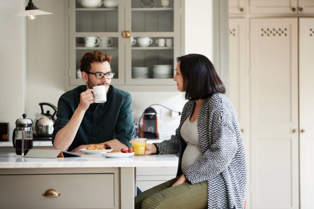 Shot of a young man having breakfast with his pregnant wife in the kitchen
