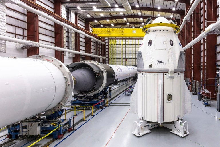 In this Dec. 18, 2018 photo provided by SpaceX, SpaceX's Crew Dragon spacecraft and Falcon 9 rocket are positioned inside the company's hangar at Launch Complex 39A at NASA's Kennedy Space Center in Florida, ahead of the Demo-1 unmanned flight test. SpaceX rockets closer to human spaceflight with this weekend???s debut of a new capsule designed for astronauts. The six-day test flight will be real in every regard, beginning with a Florida liftoff Saturday, March 2, 2019, and a docking the next day with the International Space Station. But the Dragon capsule won???t carry humans, rather a test dummy in the same white SpaceX spacesuit that astronauts will wear. (Space X via AP)