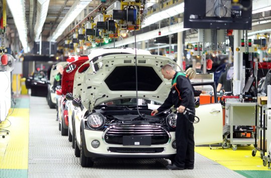 An employee inspects the engine area of a Mini automobile, produced by Bayerische Motoren Werke AG (BMW), as it reaches the end of the production line inside the final assembly plant in Oxford, U.K., on Tuesday, Sept. 20, 2016. The U.K. should maintain European Union regulations covering everything from working hours to chemicals until after the government sets out its plans for Brexit, said British manufacturers anxious to avoid a policy vacuum and safeguard access to their biggest export market. Photographer: Chris Ratcliffe/Bloomberg via Getty Images