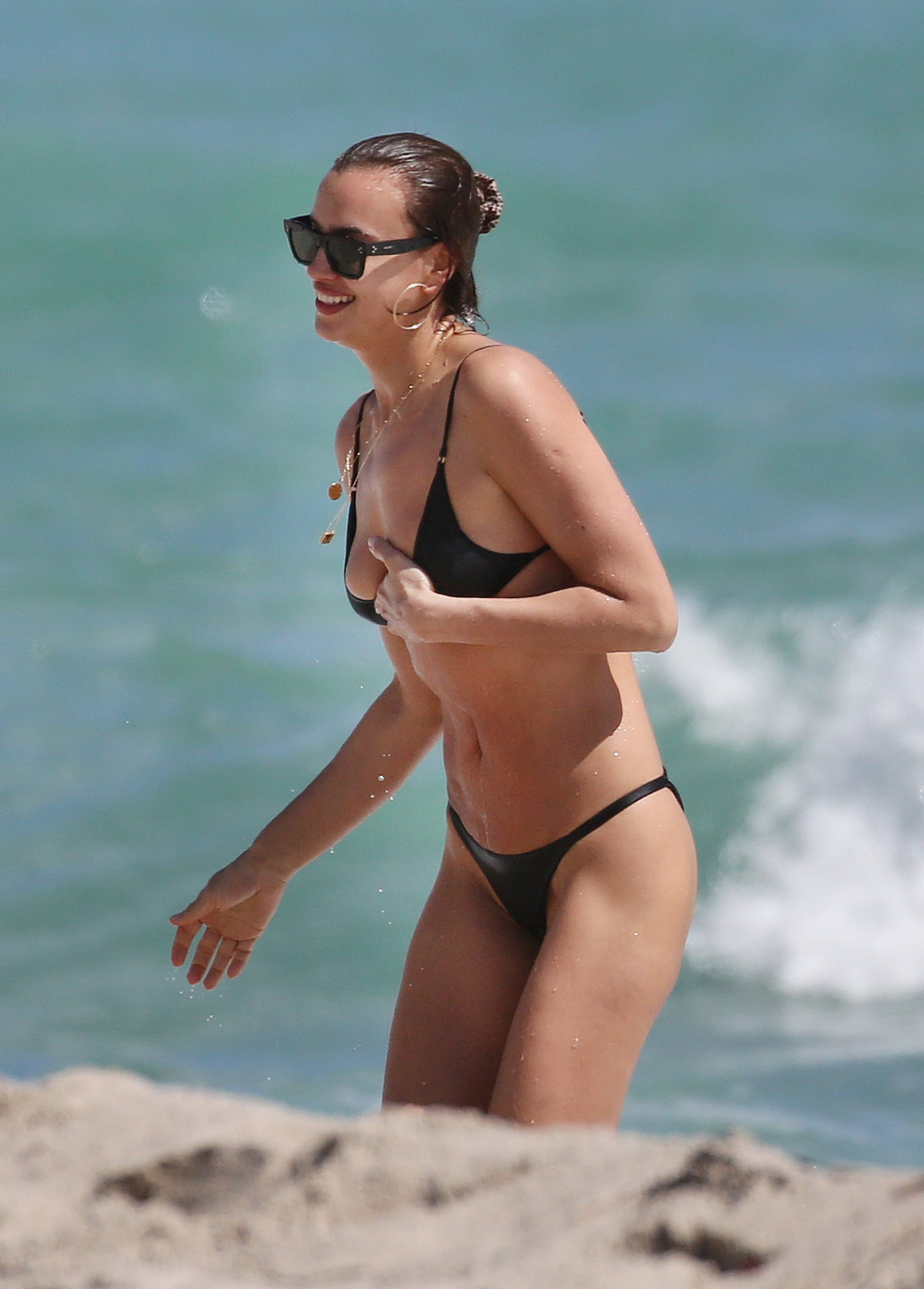 EXCLUSIVE: *NO WEB UNTIL 2045 GMT MARCH 8TH* Supermodel Irina Shayk narrowly avoids a wardrobe malfunction in a tiny black bikini as she hits the beach in Miami. The pictures of Irina showing off her sensational curves may explain why boyfriend Bradley Cooper is so smitten - and dispel Internet gossip that he???s fallen for A Star is Born co-star Lady Gaga. The 33-year-old Russian supermodel, who shares daughter Lea with the 44-year-old actor, flaunted her impossibly long legs as well as her toned midsection and her ample cleavage in the barely-there black swimwear. 07 Mar 2019 Pictured: Irina Shayk. Photo credit: MEGA TheMegaAgency.com +1 888 505 6342 (Mega Agency TagID: MEGA376513_001.jpg) [Photo via Mega Agency]