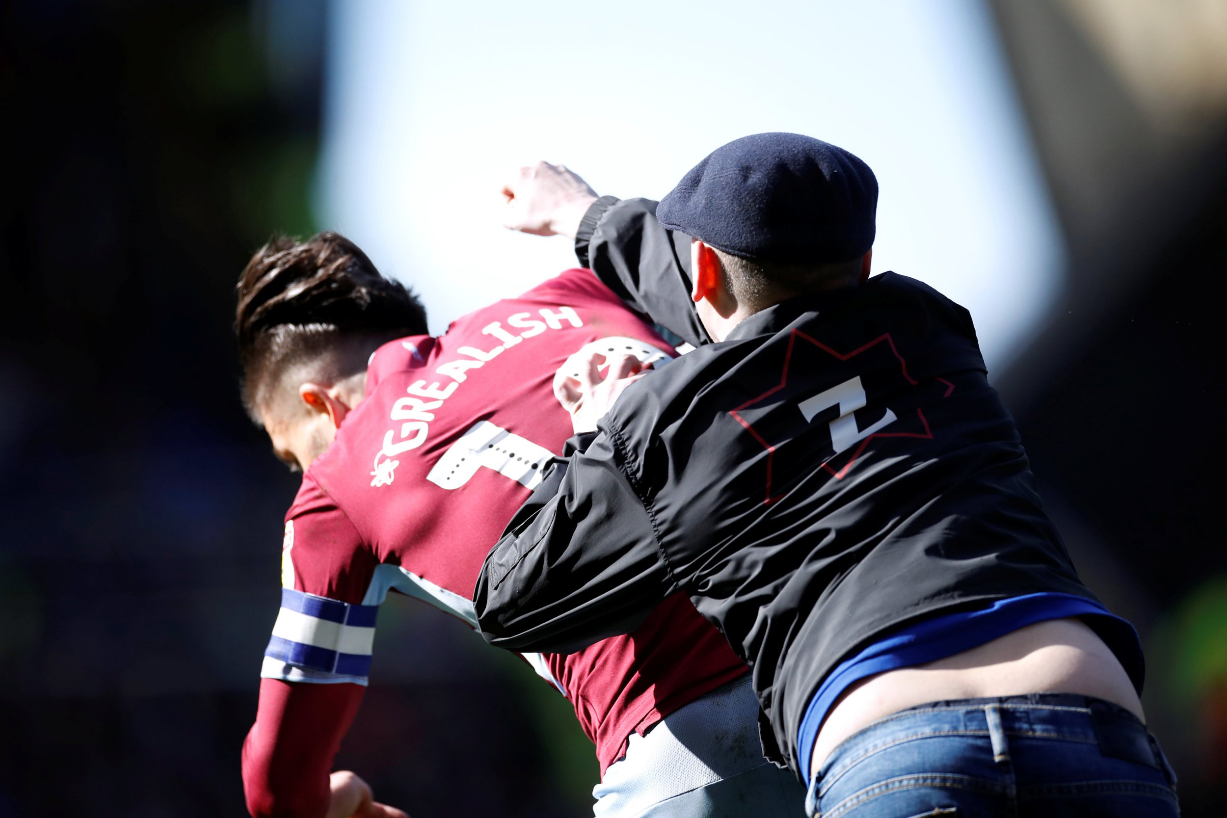 "Soccer Football - Championship - Birmingham City v Aston Villa - St Andrew's, Birmingham, Britain - March 10, 2019 A fan invades the pitch and attacks Aston Villa's Jack Grealish during the match Action Images/Carl Recine EDITORIAL USE ONLY. No use with unauthorized audio, video, data, fixture lists, club/league logos or ""live"" services. Online in-match use limited to 75 images, no video emulation. No use in betting, games or single club/league/player publications. Please contact your account representative for further details."