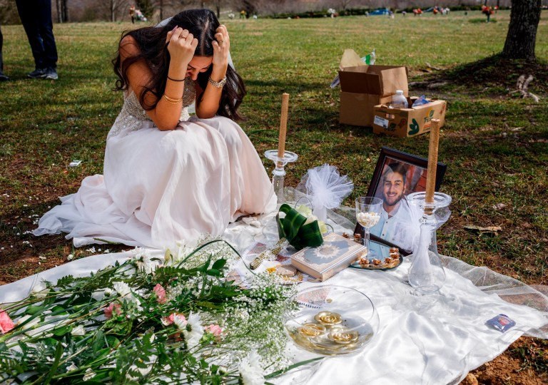 Clad in a wedding dress, Sara Baluch mourns while visiting the grave of her fiance, Mohammad Sharifi, on Sunday, March 10, 2019, the day after they were supposed to be married, at Harpeth Hills Memory Gardens in Nashville, Tenn. Sharifi, a UTC student, was shot and killed two weeks before their wedding by a man to whom he was trying to sell an Xbox. (Doug Strickland/Chattanooga Times Free Press via AP)