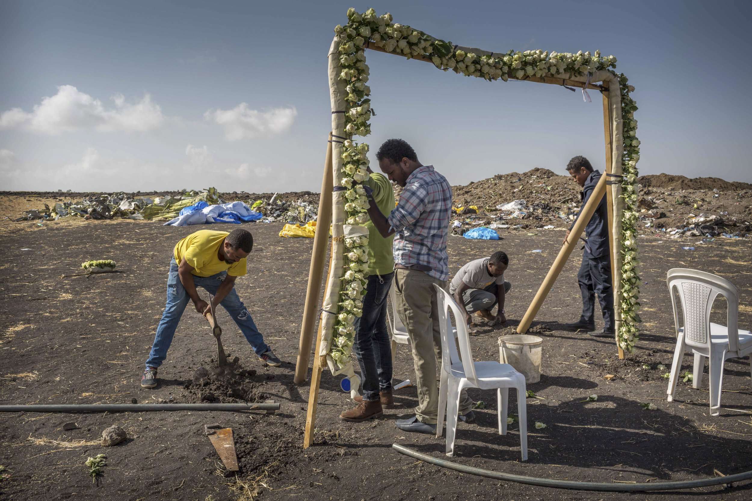 Workers erect floral installations at the scene where the Ethiopian Airlines Boeing 737 Max 8 crashed shortly after takeoff on Sunday killing all 157 on board, near Bishoftu, or Debre Zeit, south of Addis Ababa, in Ethiopia Wednesday, March 13, 2019. Much of the world, including the entire European Union, has grounded the Boeing jetliner involved in the Ethiopian Airlines crash or banned it from their airspace, leaving the United States as one of the few remaining operators of the plane involved in two deadly accidents in just five months. (AP Photo/Mulugeta Ayene)