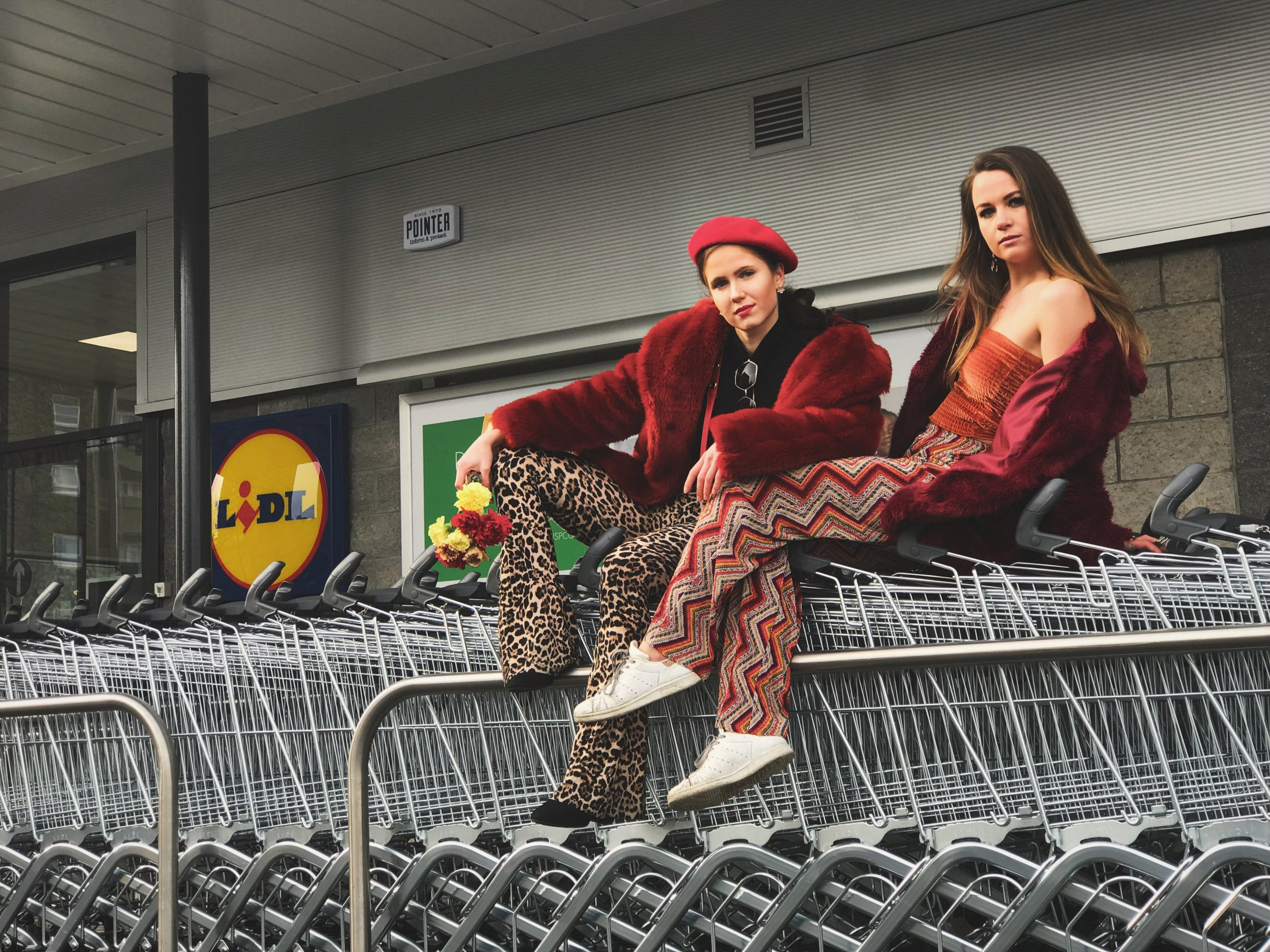 """Ella T?yryl? (left) and Bridget von Freytag Drabbe poses for a fashion shoot for student Elsa Papa at a Lidl store on Hutcheon Street in Aberdeen. See SWNS story SWSClidl; A student and her friends have carried out the world's first fashion shoot - in a Lidl. Elsa Papa, 22, a fourth year University of Aberdeen student, used her iPhone for the glamorous shots. Ella and pals Hugo, both 22, and Bridget and Emma-Jean, both 21, are spotted posing in aisles holding props such as milk and sitting next to bottles of wine. Elsa, who took the snaps using her iPhone 7 plus, said the opening of Lidl on Hutcheon Street has delighted Aberdeen students and it has become a """"big talking point""""."""