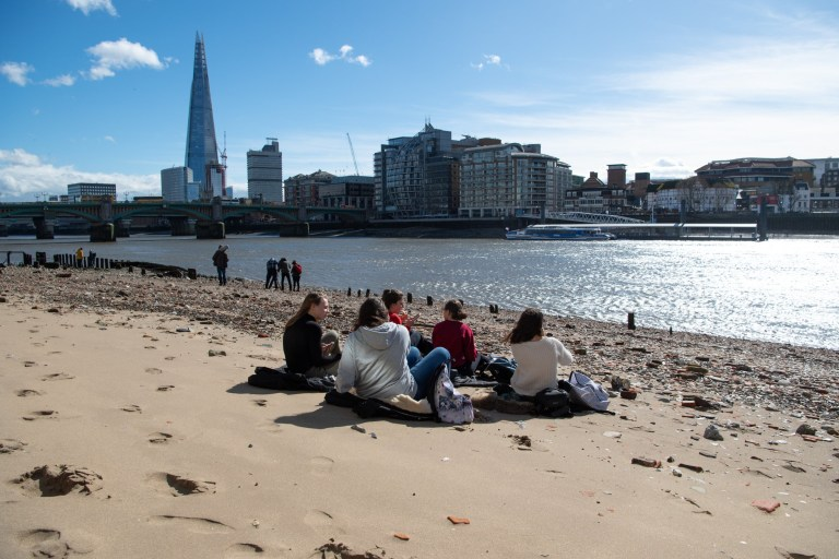 ? Licensed to London News Pictures. 14/03/2019. London, UK. Mudlarkers and sunbathers at low tide mix with workers on lunch breaks. Changeable weather sweeps up river effecting commuters and tourists, as they are hit by rain, high winds and blinding sun in the space of one hour. Photo credit: Guilhem Baker/LNP