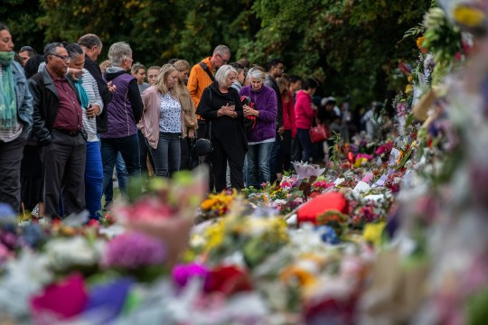 CHRISTCHURCH, NEW ZEALAND - MARCH 17: People pause next to flowers and tributes by the wall of the Botanic Gardens on March 17, 2019 in Christchurch, New Zealand. 50 people are confirmed dead, with 36 injured still in hospital following shooting attacks on two mosques in Christchurch on Friday, 15 March. 41 of the victims were killed at Al Noor mosque on Deans Avenue and seven died at Linwood mosque. Another victim died later in Christchurch hospital. A 28-year-old Australian-born man, Brenton Tarrant, appeared in Christchurch District Court on Saturday charged with murder. The attack is the worst mass shooting in New Zealand's history. (Photo by Carl Court/Getty Images)