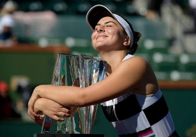 Bianca Andreescu, of Canada, smiles as she hugs her trophy after defeating Angelique Kerber, of Germany, in the women's final at the BNP Paribas Open tennis tournament Sunday, March 17, 2019, in Indian Wells, Calif. Andreescu won 6-4, 3-6, 6-4. (AP Photo/Mark J. Terrill)