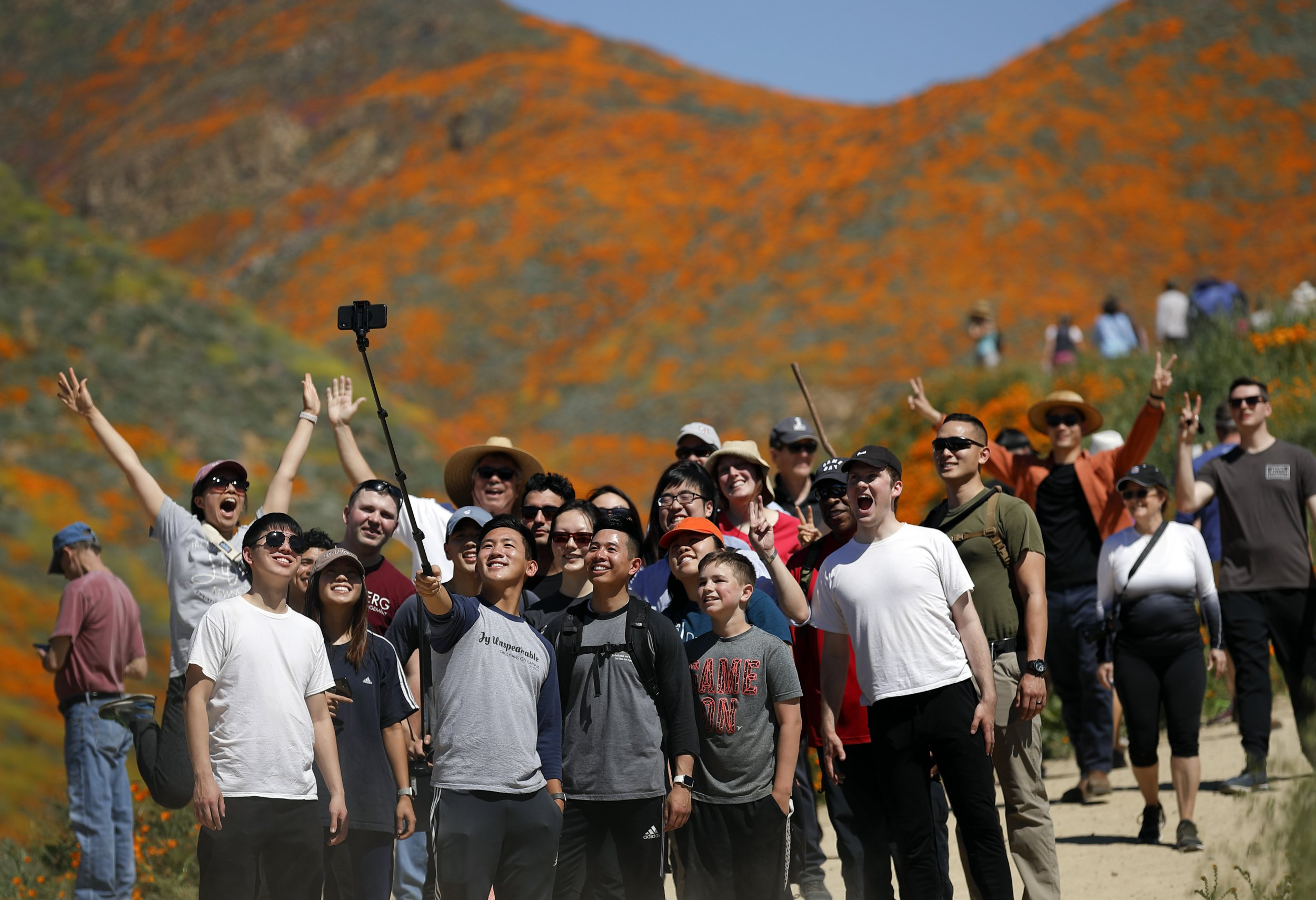 People pose for a picture among wildflowers in bloom Monday, March 18, 2019, in Lake Elsinore, Calif. About 150,000 people flocked over the weekend to see this year's rain-fed flaming orange patches of poppies lighting up the hillsides near Lake Elsinore, a city of about 60,000 residents. The crowds became so bad Sunday that Lake Elsinore officials closed access to poppy-blanketed Walker Canyon. By Monday the #poppyshutdown announced by the city on Twitter was over and the road to the canyon was re-opened. (AP Photo/Gregory Bull)