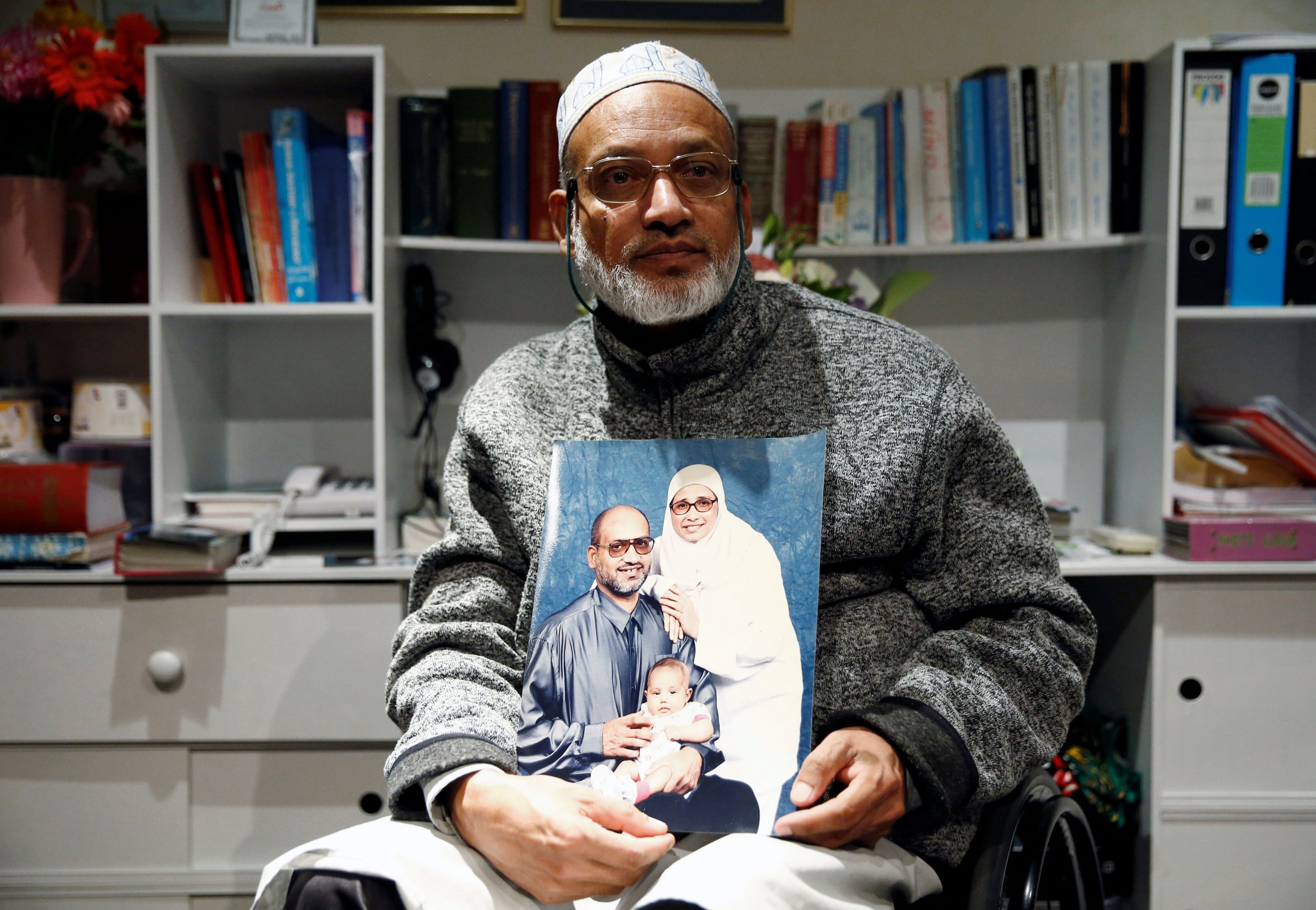 Al Noor mosque shooting survivor Farhid Ahmed poses with a photo of his wife Husna, who was killed in the attack, after an interview with Reuters in Christchurch, New Zealand March 18, 2019. Picture taken March 18, 2019. REUTERS/Edgar Su