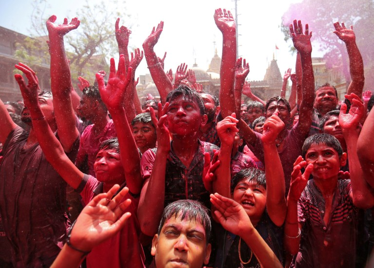 Hindu devotees raise their hands daubed in colours as they pray on a temple premises during Holi celebrations in Ahmedabad, India, March 20, 2019. REUTERS/Amit Dave
