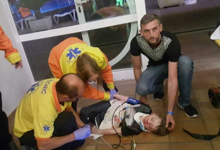 Undated handout photo issued by Slater and Gordon Solicitors of six-year-old boy Oscar Donnelly, being treated by medical staff and his father Luke, after an arcade game toppled over and crushed him on a family holiday, leaving him with brain damage and a paralysed face. PRESS ASSOCIATION Photo. Issue date: Wednesday March 20, 2019. Oscar was also left with a rare form of diabetes after he was knocked unconscious by the 6ft darts machine which pinned him to the ground in the Spanish resort of Lloret de Mar. See PA story ACCIDENT Lloret. Photo credit should read: Slater and Gordon/PA WireNOTE TO EDITORS: This handout photo may only be used in for editorial reporting purposes for the contemporaneous illustration of events, things or the people in the image or facts mentioned in the caption. Reuse of the picture may require further permission from the copyright holder.