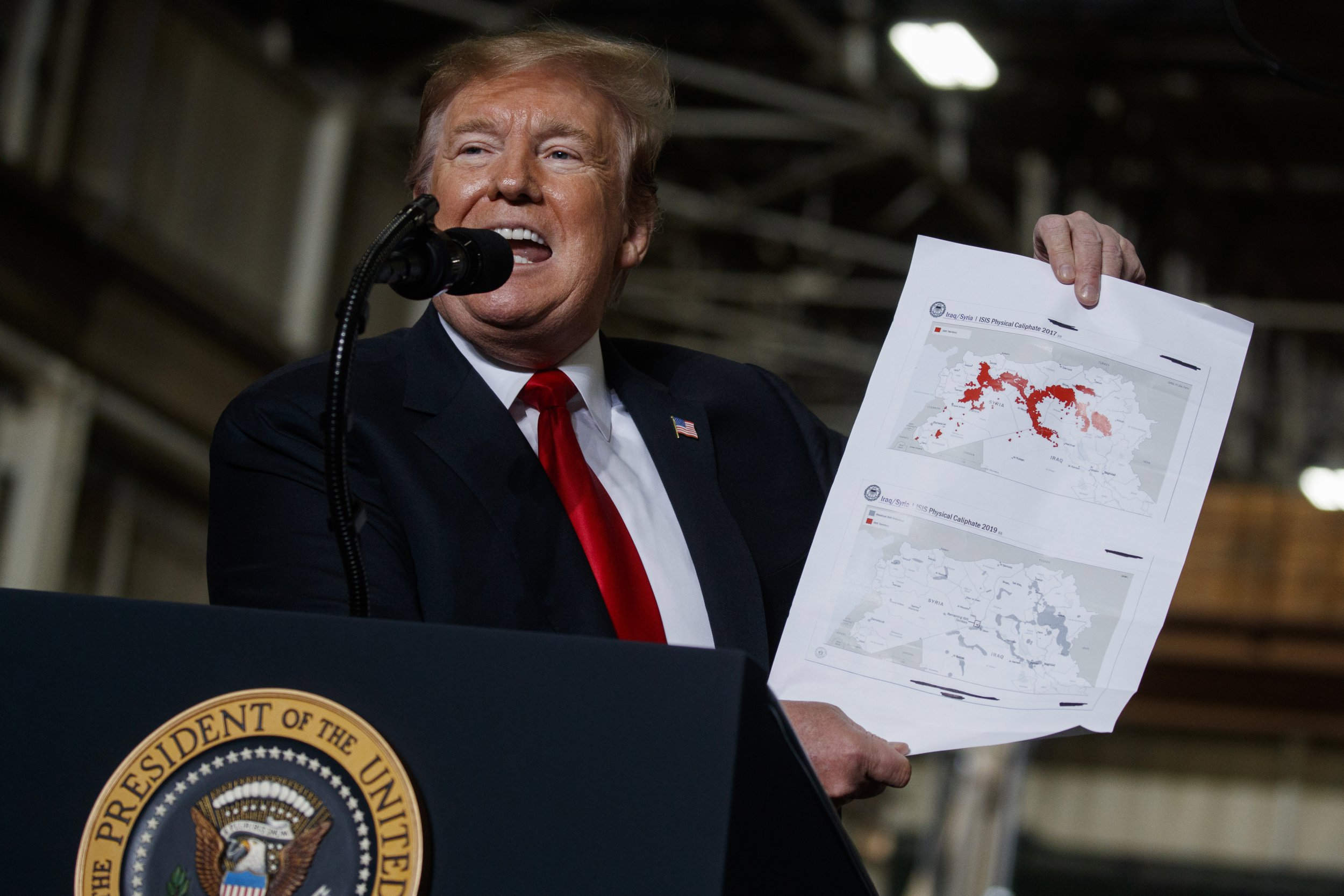 President Donald Trump holds up a chart documenting ISIS land loss in Iraq and Syria as delivers remarks at the Lima Army Tank Plant, Wednesday, March 20, 2019, in Lima, Ohio. (AP Photo/Evan Vucci)