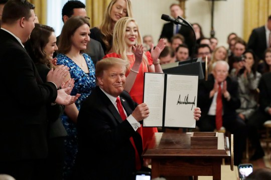 """President Donald Trump holds up an executive order on """"improving free inquiry, transparency, and accountability on campus"""" after signing in the East Room of the White House, Thursday, March 21, 2019, in Washington. (AP Photo/Evan Vucci)"""
