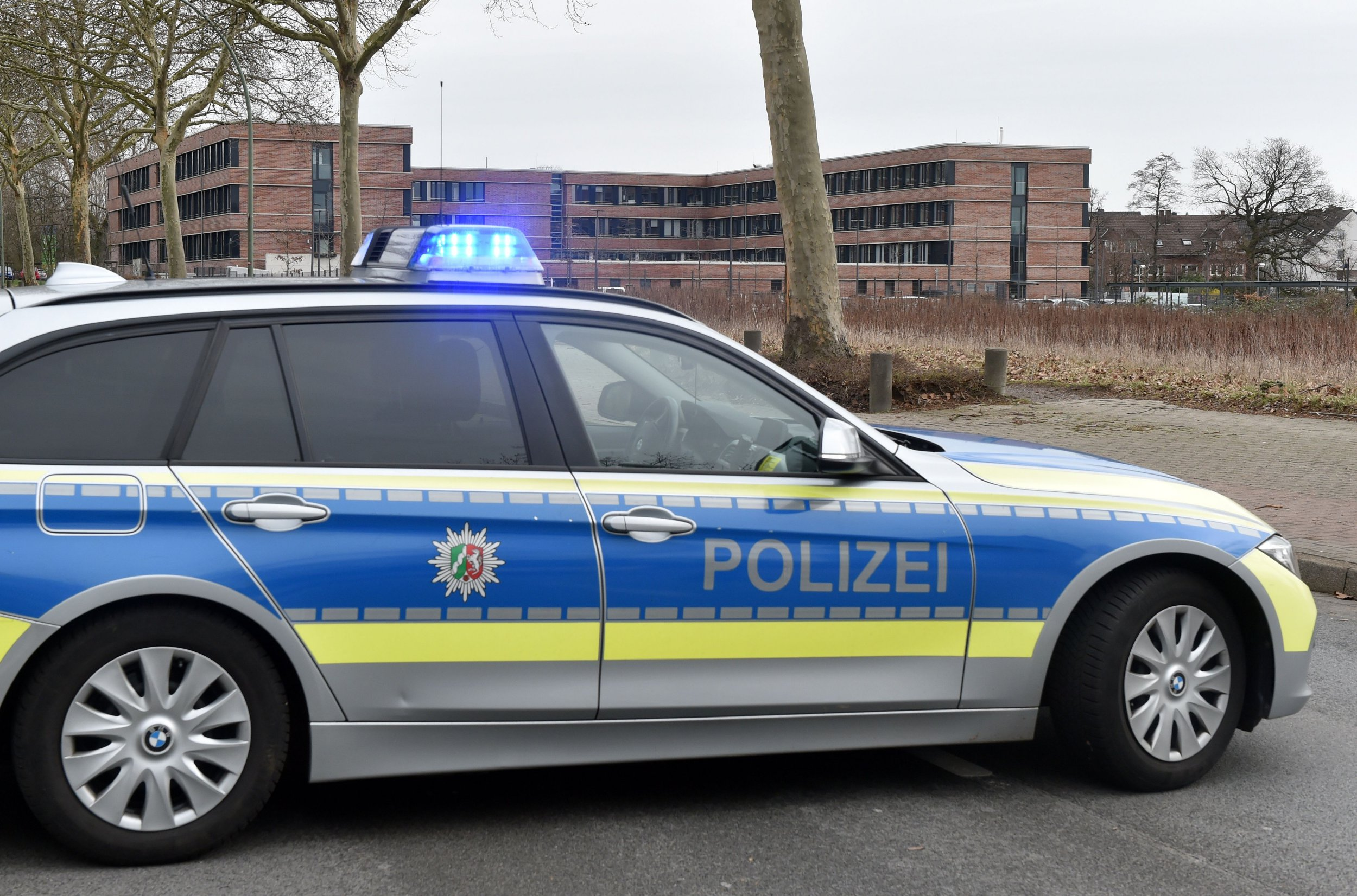 A picture taken on March 12, 2019 in Gelsenkirchen shows a German police car blocking the access to the tax office after its evacuation due to an email containing a bomb threat. - German authorities were on March 14, 2019 investigating over 100 threatening emails apparently sent by far-right sympathisers to lawyers, politicians, journalists and even a pop star. (Photo by Caroline Seidel / dpa / AFP) / Germany OUT (Photo credit should read CAROLINE SEIDEL/AFP/Getty Images)