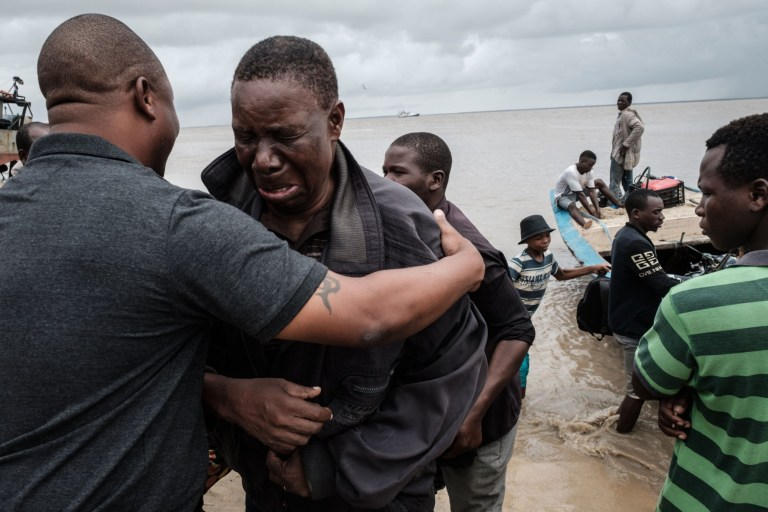 Manuel Machacawa Maezane (2nd L), 76, cries as he meets his son Aristides (L) after being evacuated from Buzi, on the beach in Beira, Mozambique, on March 23, 2019. - The death toll in Mozambique on March 23, 2019 climbed to 417 after a cyclone pummelled swathes of the southern African country, flooding thousands of square kilometres, as the UN stepped up calls for more help for survivors. Cyclone Idai smashed into the coast of central Mozambique last week, unleashing hurricane-force winds and rains that flooded the hinterland and drenched eastern Zimbabwe leaving a trail of destruction. (Photo by Yasuyoshi CHIBA / AFP)YASUYOSHI CHIBA/AFP/Getty Images