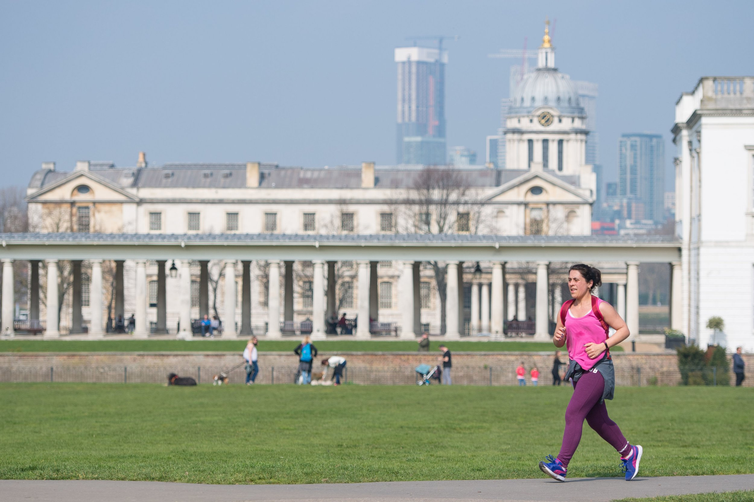A runner passes the Old Naval College in Greenwich Park, London, as people enjoy a day of warm weather. PRESS ASSOCIATION Photo. Picture date: Saturday March 30, 2019. Photo credit should read: Dominic Lipinski/PA Wire