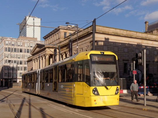 A view of a yellow tram with Manchester Art Gallery behind.
