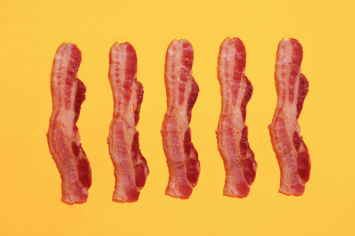 strips of bacon on a colourful yellow background