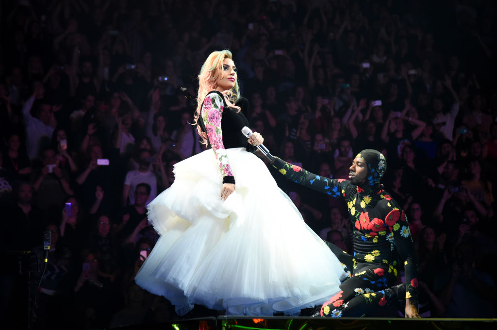 Lady Gaga performing with backing dancer Asiel Hardison on her Joanne World Tour