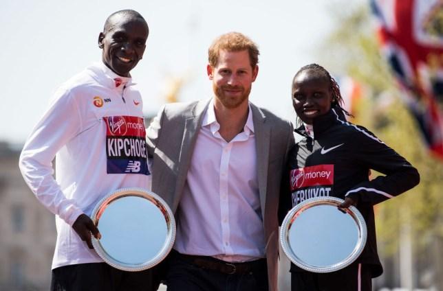 Eliud Kipchoge and Vivian Cheruiyot pose with their trophies alongside Prince Harry after winning the 2018 London Marathon