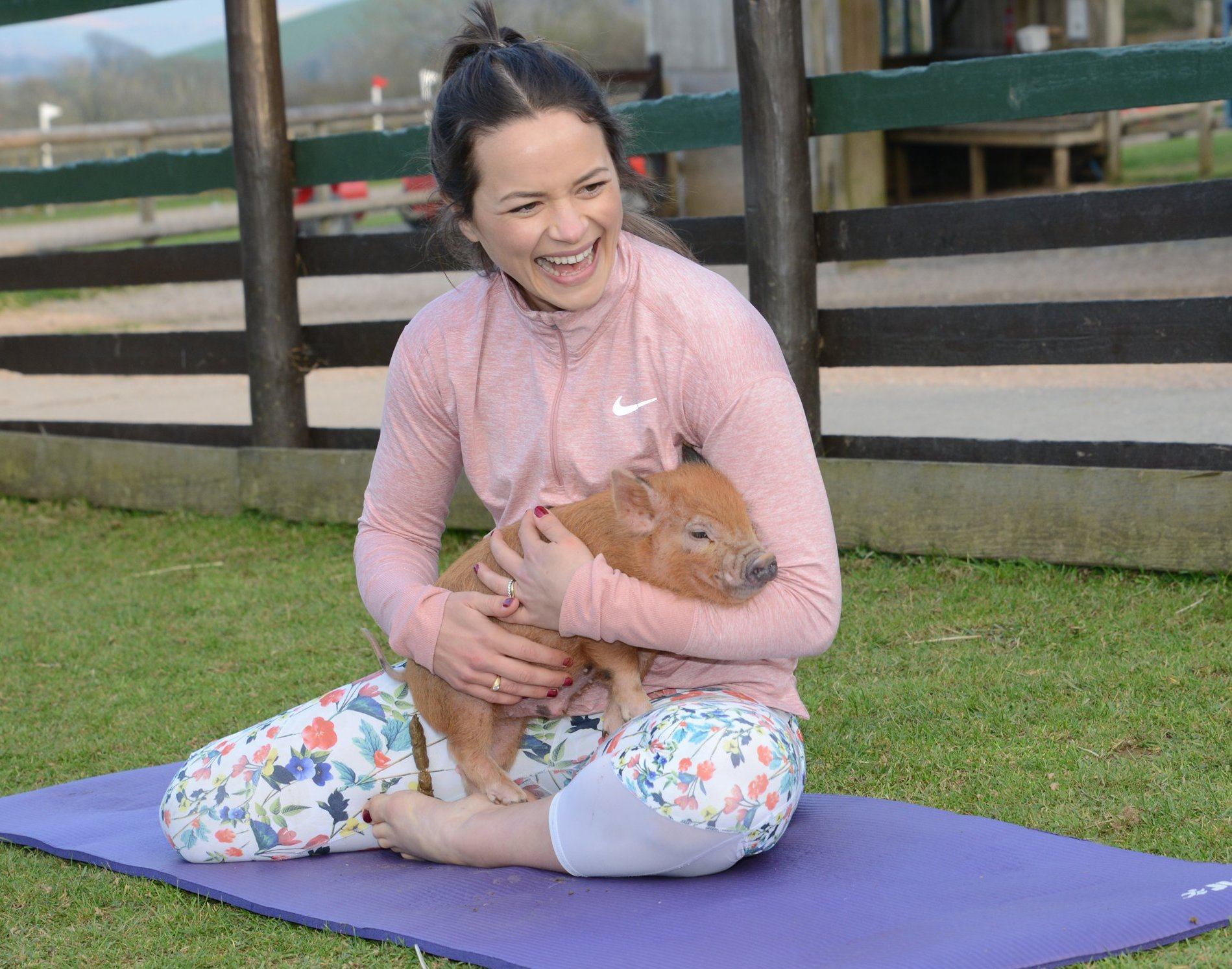 Harry cuddles a pig while sitting on a pilates mat