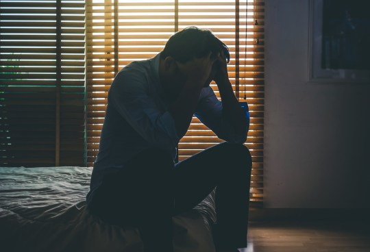 depressed man sitting head in hands on the bed in the dark bedroom with low light environment, dramatic concept; Shutterstock ID 627491903; Purchase Order: -