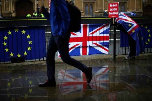 A person walks past an EU and a British flag in London, Britain, April 2, 2019. REUTERS/Hannah Mckay