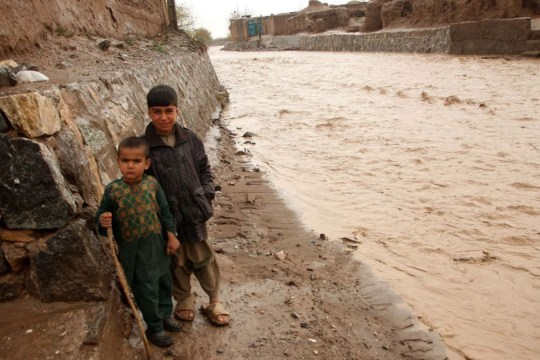 HERAT, AFGHANISTAN - MARCH 30: Kids gesture to camera near a flooded area due to heavy rainfall in Herat, Afghanistan on March 30, 2019. At least 15people lost their lives after flood. (Photo by Mir Ahmad Firooz/Anadolu Agency/Getty Images)