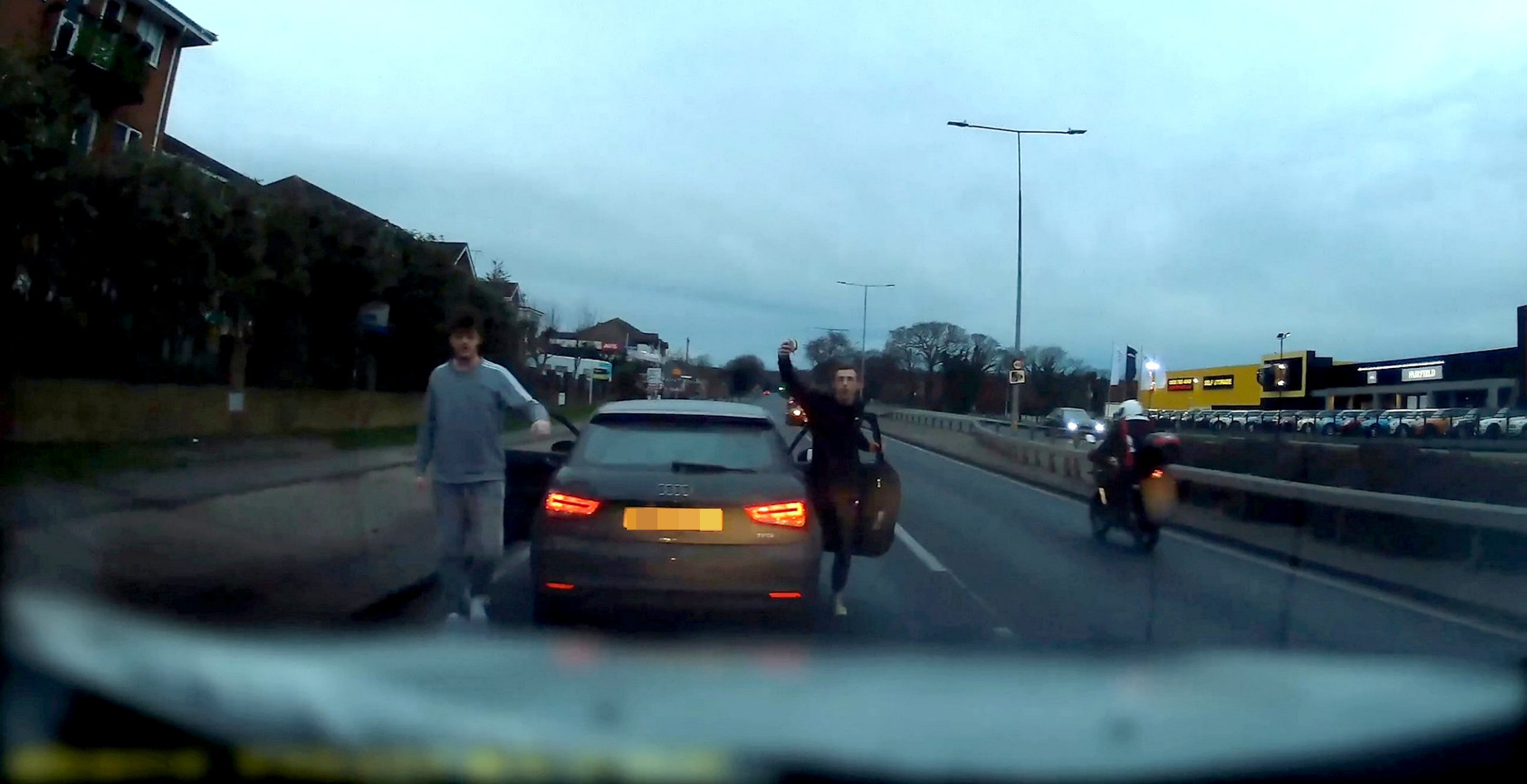 Video grab of the first stop performed by two yobs, one holding a CUPCAKE, in a stolen Audi on the A127 between the Bellhouse junction and the Rayleigh Weir, who continually threatened and chased a van driver on the morning of January 13.See SWNS story SWSCrage. Police are appealing for information after two thugs forced a driver to stop on the A127 and threatened him repeatedly.The incident happened on the A127 between the Bellhouse junction and the Rayleigh Weir roundabout at about 8.10am on Sunday, January 13.In a shocking dash cam clip, the black Audi can be seen to repeatedly force the driver to stop before he gets out of the car with his passenger and threaten the driver who is then forced to drive round them.