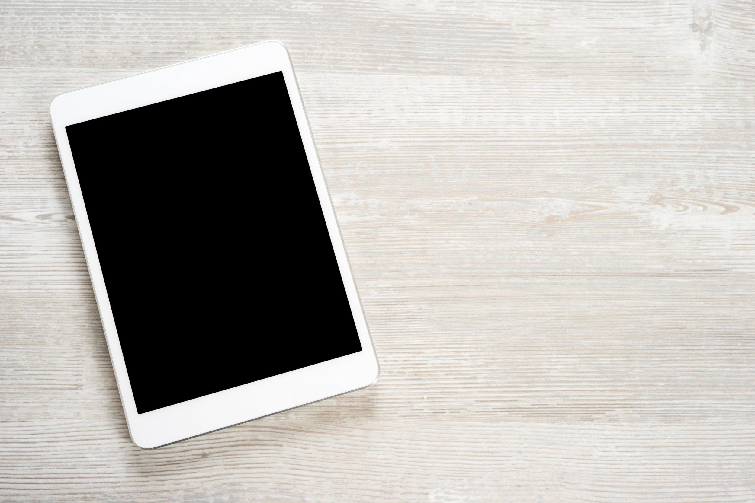 White digital tablet on wooden table