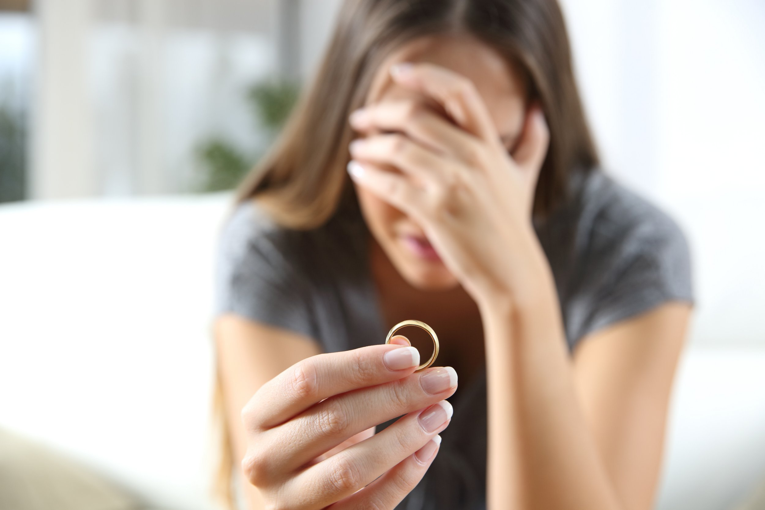 Closeup of a single sad wife after divorce lamenting holding the wedding ring in a house interior; Shutterstock ID 511166536; Purchase Order: -