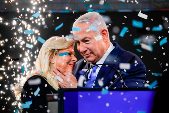 TOPSHOT - Israeli Prime Minister Benjamin Netanyahu embraces his wife Sara as confetti and fireworks are blown during his appearance before supporters at his Likud Party headquarters in the Israeli coastal city of Tel Aviv on election night early on April 10, 2019. (Photo by Thomas COEX / AFP)THOMAS COEX/AFP/Getty Images