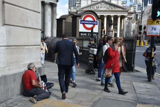 LONDON, ENGLAND - AUGUST 25: Members of the public walk by as a man plays a saxophone for money to help his sick wife outside Bank tube station close to the Bank of England on August 25, 2017 in London, England. (Photo by John Keeble/Getty Images)