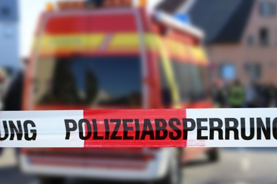 Police cordon tape with a ambulance in the background (Germany)