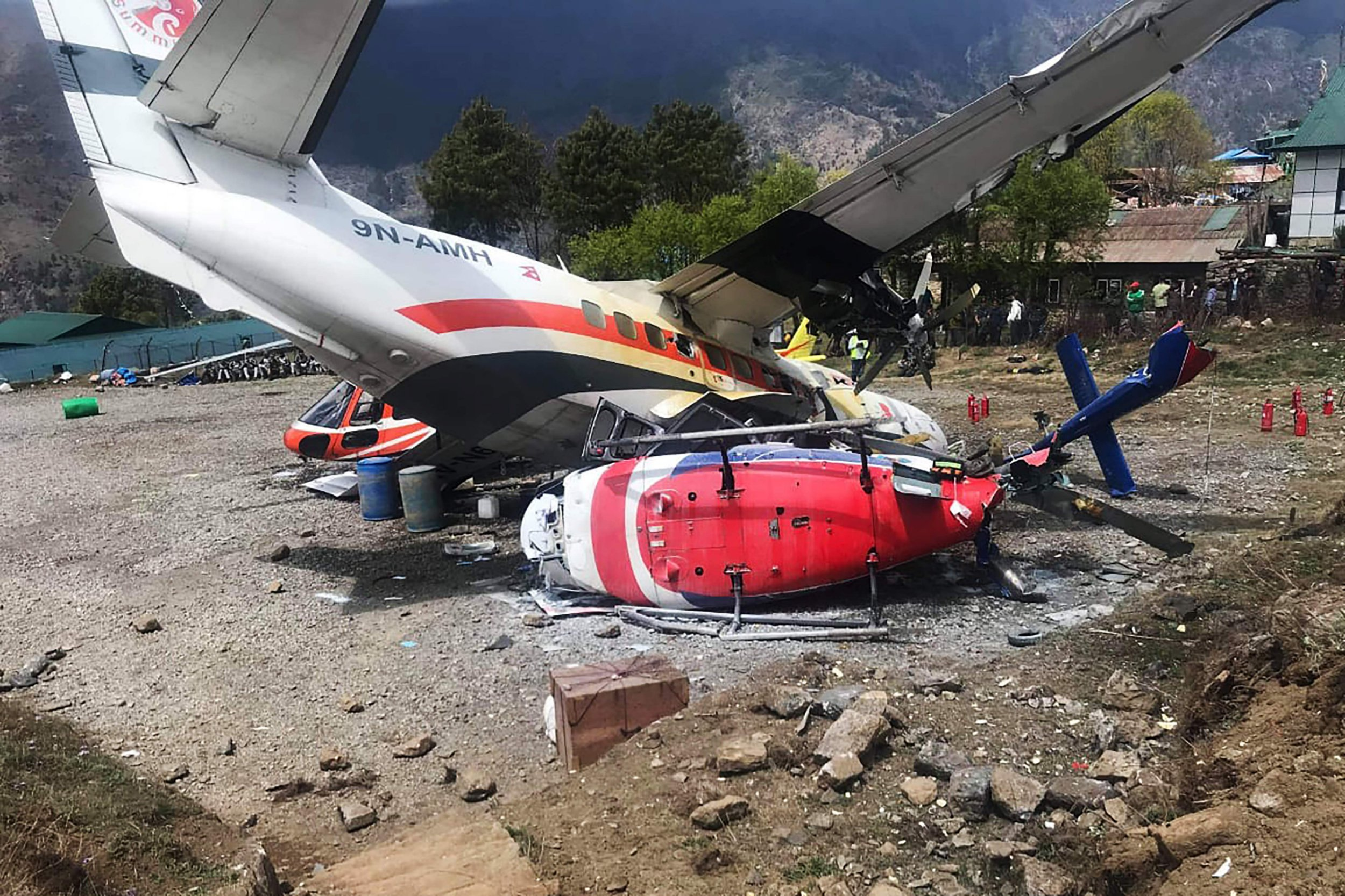 TOPSHOT - A Summit Air Let L-410 Turbolet aircraft bound for Kathmandu is seen after it hit two helicopters during take off at Lukla airport, the main gateway to the Everest region. - A small plane veered off the runway and hit two helicopters while taking off near Mount Everest on April 14, killing three people and injuring three, officials said. (Photo by STR / AFP)STR/AFP/Getty Images