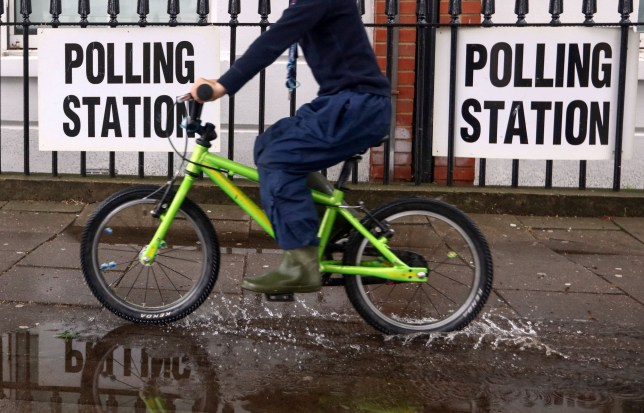 A child on a bicycle passes signs for a polling station