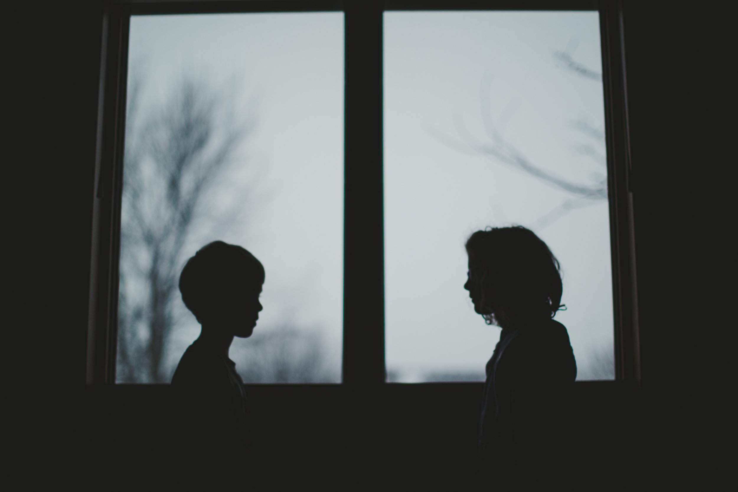 Little child and small lady mount in front of a window looking during any other formulating dual silhouettes in of a window with cloudy skies behind them.