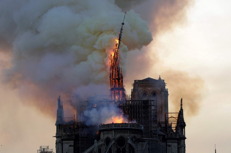 The steeple of the landmark Notre-Dame Cathedral collapses as the cathedral is engulfed in flames in central Paris on April 15, 2019. - A huge fire swept through the roof of the famed Notre-Dame Cathedral in central Paris on April 15, 2019, sending flames and huge clouds of grey smoke billowing into the sky. The flames and smoke plumed from the spire and roof of the gothic cathedral, visited by millions of people a year. A spokesman for the cathedral told AFP that the wooden structure supporting the roof was being gutted by the blaze. (Photo by Geoffroy VAN DER HASSELT / AFP)GEOFFROY VAN DER HASSELT/AFP/Getty Images