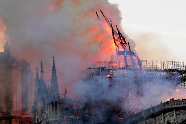 epa07508757 The spire collapses while flames are burning the roof of the Notre-Dame Cathedral in Paris, France, 15 April 2019. A fire started in the late afternoon in one of the most visited monuments of the French capital. EPA/IAN LANGSDON