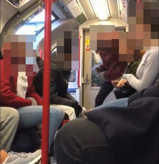 The footage begins with the girl in the red jacket telling the commuter next to her to get off the phone (Picture: Triangle News/Lee Harris/Facebook)